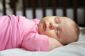 pic of sweet dreams  - A sweet one month old newborn baby girl is sleeping on her back in her crib swaddled in a pink blanket - JPG