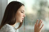 Sad Woman Looking Rain Through A Window poster