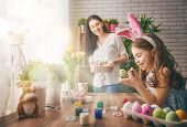Постер, плакат: Happy easter A mother and her daughter painting Easter eggs Happy family preparing for Easter Cut