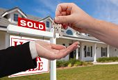 foto of real-estate agent  - Handing Over the House Keys in Front of Sold New Home Against a Blue Sky - JPG