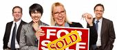 Real Estate Team Behind with Blonde Woman in Front Holding Keys and Sold For Sale Real Estate Sign I