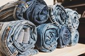 background of a stack rolled jeans on shelf poster