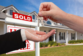 pic of real-estate agent  - Handing Over the House Keys in Front of Sold New Home Against a Blue Sky - JPG