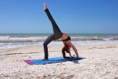 stock photo of dhanurasana  - an athletic brown haired woman is doing yoga exercise one leg full wheel pose or Urdhva Dhanurasana also known as upward bow posture on an empty beach - JPG