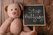 Chalkboard with text STOP BULLYING and toy on wooden background poster