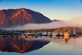 Fishing boats in harbor at midnight sun and fog in Northern Norway, Lofoten Island, Norway - Mountai poster