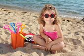 little girl with sunglasses sitting on beach