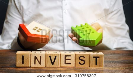 poster of Wooden Blocks With The Word Invest And Houses In The Hands Of A Businessman. The Concept Of Investin