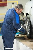 car mechanic installing wheel alignment equipment during suspension adjustment and automobile wheel