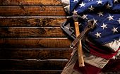 Old and worn work tools on large American flag - Labor day background poster