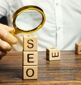 Blocks With The Word Seo And A Magnifying Glass In The Hand Of A Businessman. Search Engine Optimiza poster