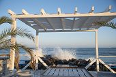 White Wooden Veranda On The Beach.in The Background, The Waves Break On The Rocks poster