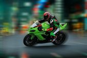 Motorcycle Rider In Helmet And Gear Racing At High Speed On The Nighttime Background With Motion Blu poster