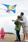 Happy dad and son flying kite together at  beach