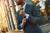 Stylish Man. Confident Businessman In Full Suit Adjusting His Sleeve While Standing Outdoors poster