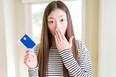 Beautiful Asian woman holding credit card cover mouth with hand shocked with shame for mistake, expr poster