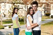 picture of envy  - outdoor photo of a young woman jealous on a happy couple - JPG