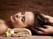 Masseur doing massage the head and hair for an woman in spa salon poster