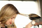 Blonde Woman Getting Hairstyle Closeup Photography. Iron Tool To Straight Hair. Styling Hairdo For G poster
