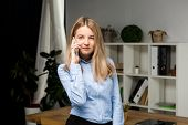 Portrait Of Businesswoman With Mobile Phone Standing At Office. Young Caucasian Businesswoman Holdin poster