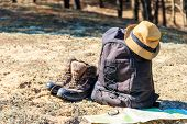 Tourist Backpack With Hiking Boots, Hat, Compass And Map On The Glade In Pine Forest. Trekking Hike  poster