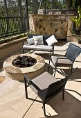 Custom Home backyard - chairs, fire-pit, and Italian style stone waterfall