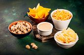 Assortment Of Unhealthy Beer Snacks: Chips, Nachos, Pistachios, Cheese In Bowls, Top View, Copy Spac poster