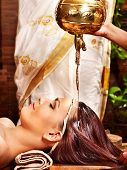 stock photo of panchakarma  - Young woman having oil Ayurveda spa treatment - JPG