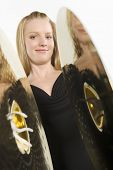 Close up of a beautiful Caucasian woman banging cymbal isolated over white background