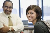 stock photo of professor  - Portrait of professor and student smiling together in library - JPG