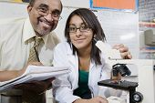 Portrait of professor and female student with microscope