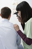 picture of otoscope  - Female doctor checking patient ear with otoscope - JPG