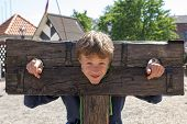 foto of torture  - a boy trapped in a medieval torture device - JPG
