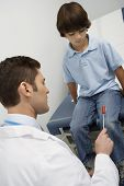 Male doctor checking boy's knee with reflex hammer