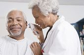 foto of otoscope  - Senior female doctor checking patient - JPG