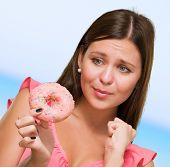 Worried Woman Holding Doughnut against a blue background