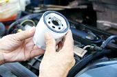 picture of grease  - Hand holding a car ingine oil filter