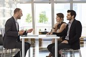 stock photo of work crew  - Happy corporate business people talking at meeting at office - JPG