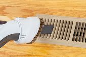 picture of floor heating  - Horizontal photo of vacuum cleaning heater floor vent with Red Oak Floors in background