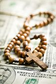 rosary beads lying on us dollars backround