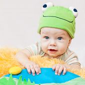foto of cute frog  - cute baby playing in the hat frog lying on his stomach on a white background - JPG
