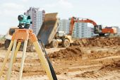 stock photo of theodolite  - Surveying measuring equipment level theodolite on tripod at construction building area site - JPG
