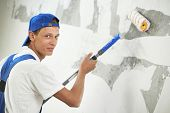 stock photo of overhauling  - One painter with paint roller making wall prime coating  at home repair renovation work - JPG