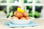 Eggs in plate on wooden table on window background