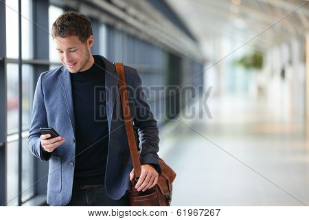 Man on smart phone - young business man in airport. Casual urban professional businessman using smar poster