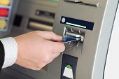stock photo of debit card  - male hand businessman inserts credit card into the ATM and withdraws money - JPG