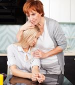 Mother soothes sad daughter. Mature woman calm young woman