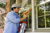 stock photo of insulator  - Man on ladder caulking outside window to insulate against the weather - JPG