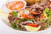 picture of endive  - Grilled prawns with a green leafy lettuce and endive salad and a jacket potato topped with sour cream served on a white plate close up high angle view on white - JPG