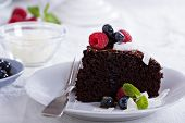 foto of vegan  - Vegan chocolate cake with berries and coconut on top - JPG